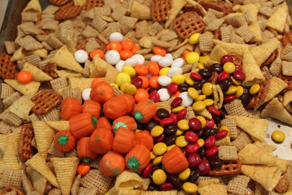 adding candy to Autumn Candy Corn M&M snack mix