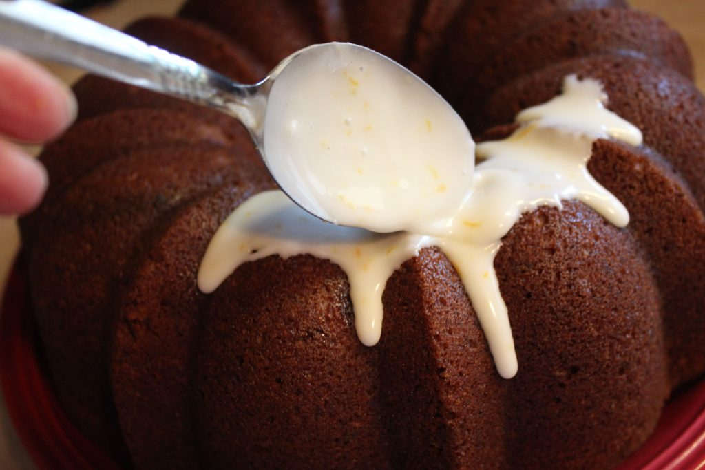spooning glaze on Apple Bundt Cake