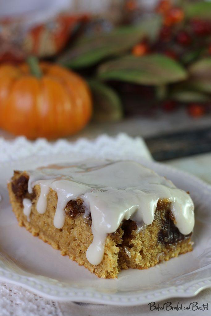 Slice of Pumpkin Spiced Cinnamon Roll Cake oozing with Cream Cheese glaze