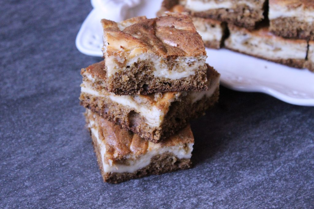 Gingerbread Cheesecake Brownies stacked next to a platter