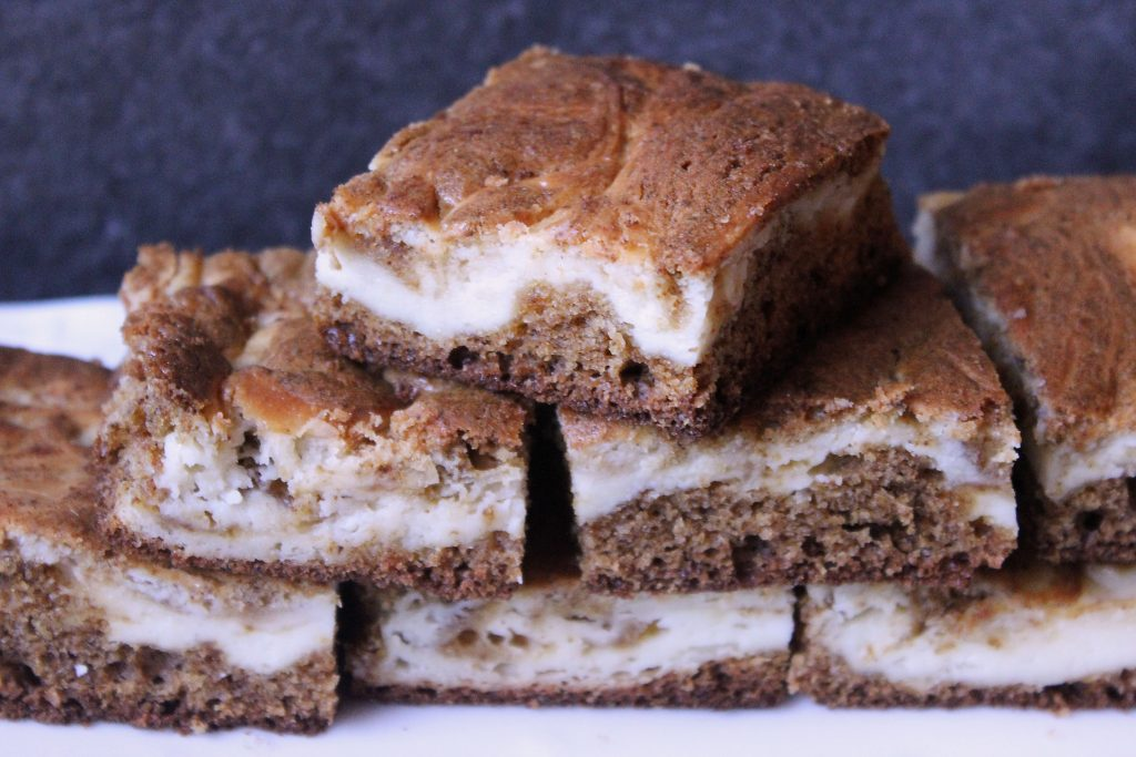 Gingerbread Cheesecake Brownies stacked on a platter