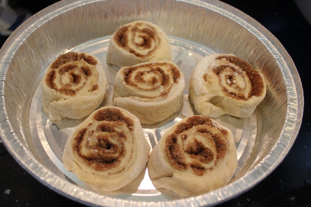 cinnamon rolls in aluminum pan before rising