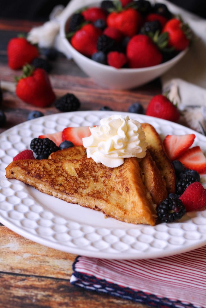 Brioche French Toast on a plate with berries and whipped cream