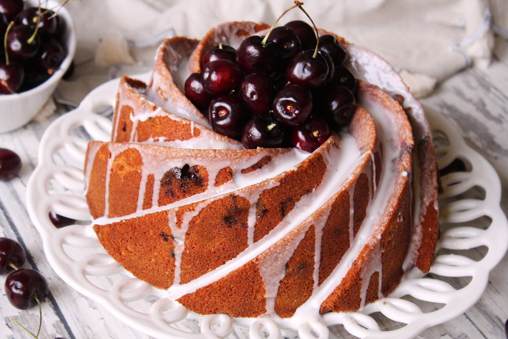 Cherry Amaretto Bundt Cake on a white place with fresh cherries on top.