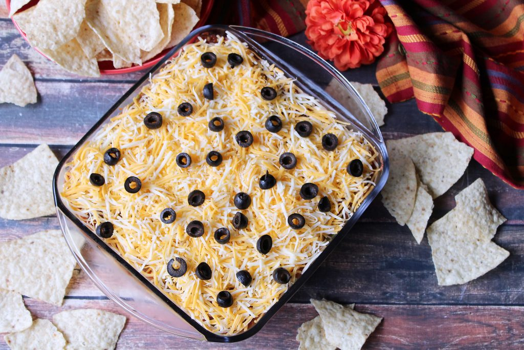 Tex Mex Layered Dip surrounded by tortilla chips