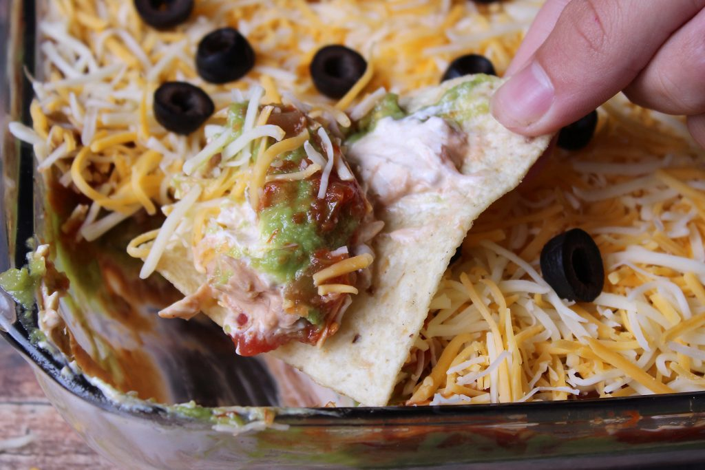 Tex Mex Layered Dip being scooped up