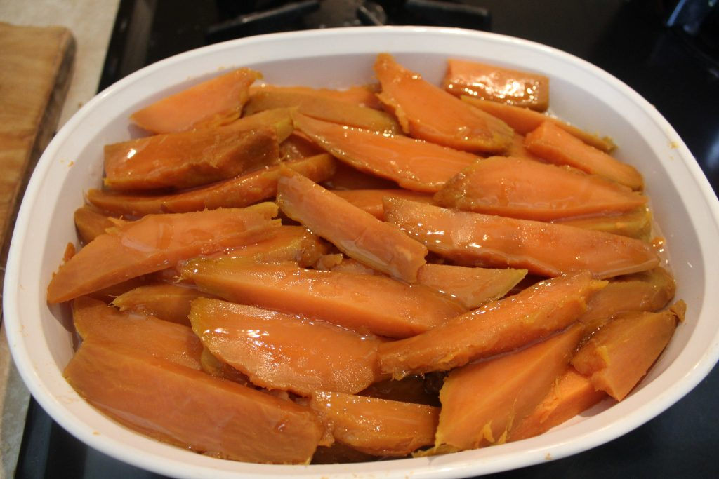 slices of sweet potatoes in baking dish with simple syrup
