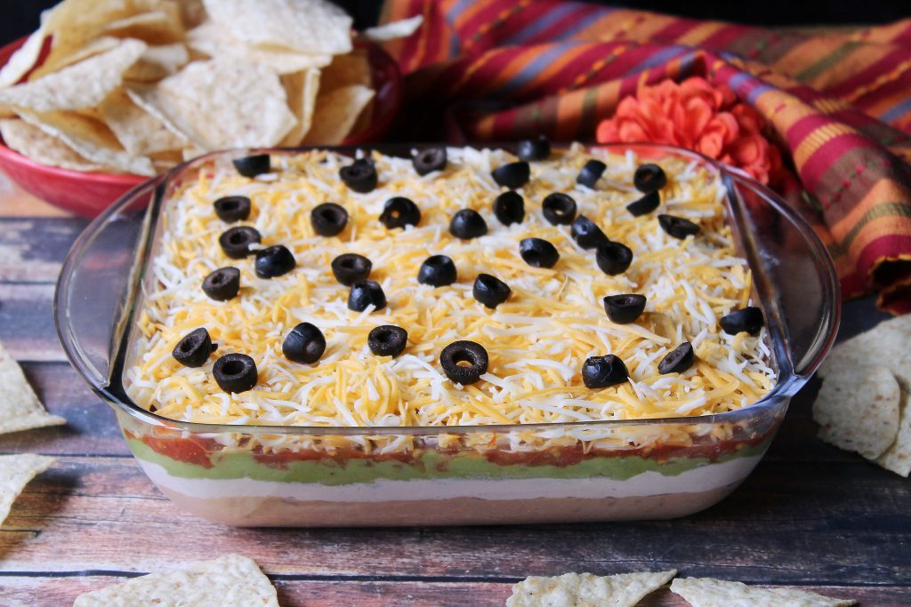 Tex Mex layered dip in a clear serving dis