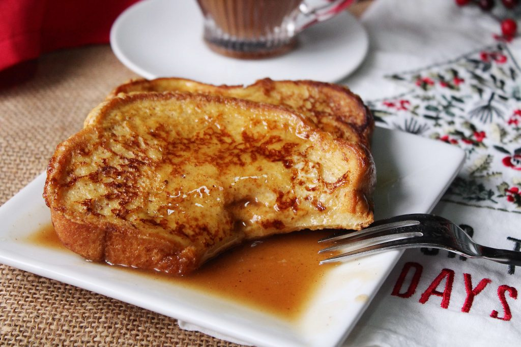 Eggnog French Toast on a plate with syrup and a bite taken out