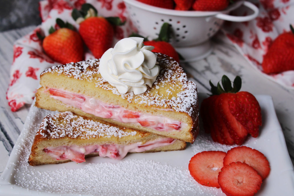 Strawberry Cheesecake French Toast on a white plate with whipped cream and strawberries