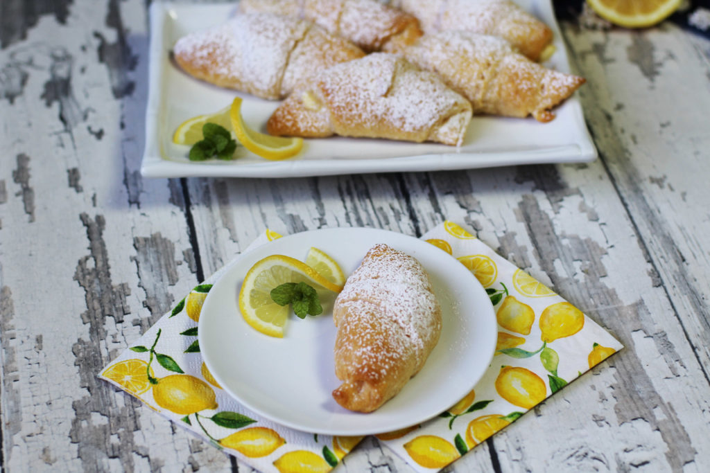 Lemon Cream Cheese Crescents on a white plate with a lemon wedge