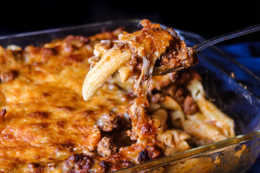 Easy Baked Ziti being scooped out of the baking dish