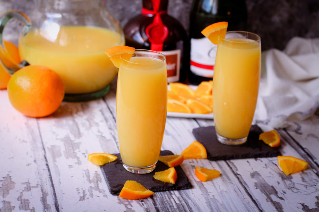 2 Grand Mimosas on in champagne flutes garnished with oranges
