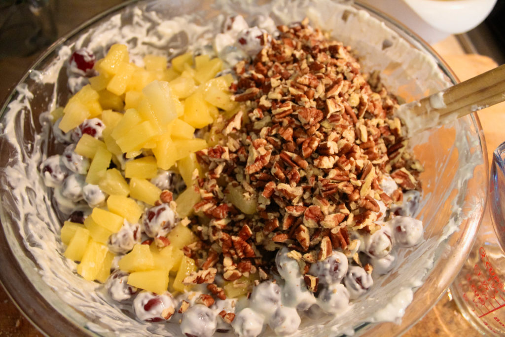 adding pecans and pineapple to the grape salad