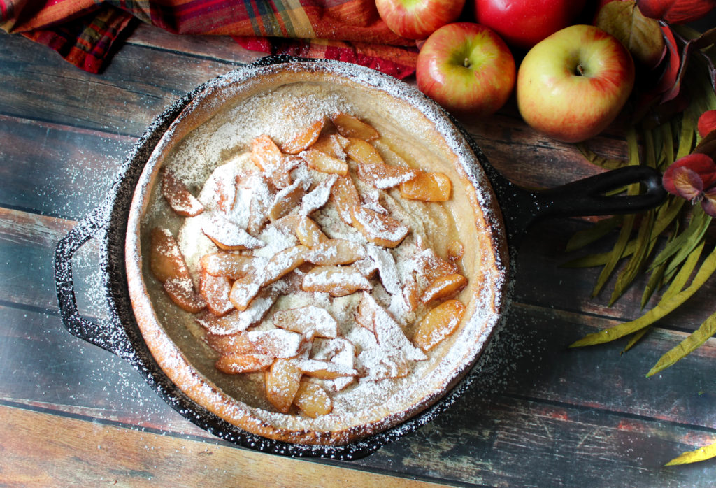 Apple Dutch Baby in a black skillet with powdered sugar sprinkled on top.