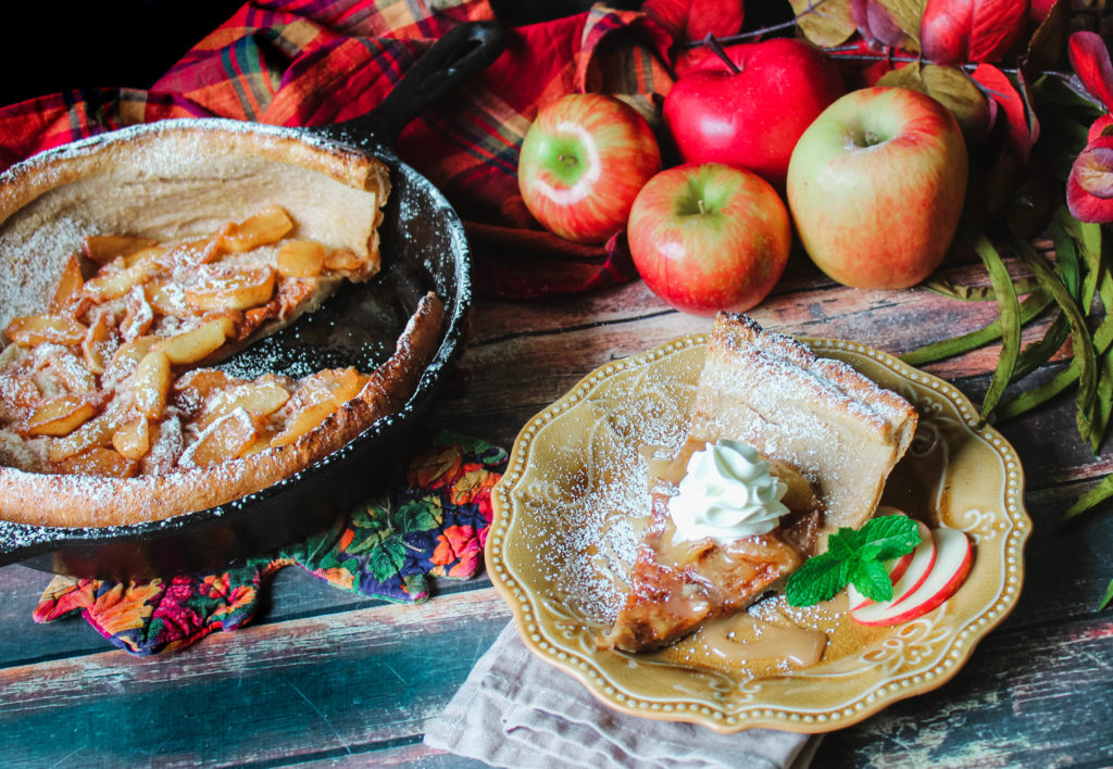 Apple Dutch Baby slice in a brown plate topped with whipped cream