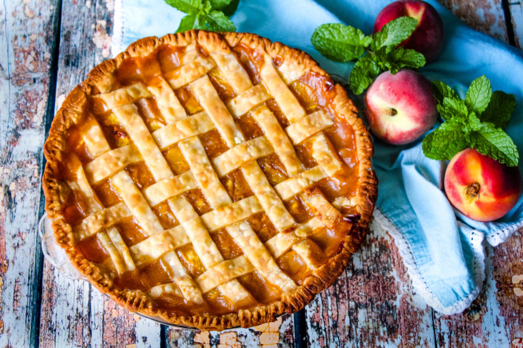 Whole fresh peach pie with lattice crust on top