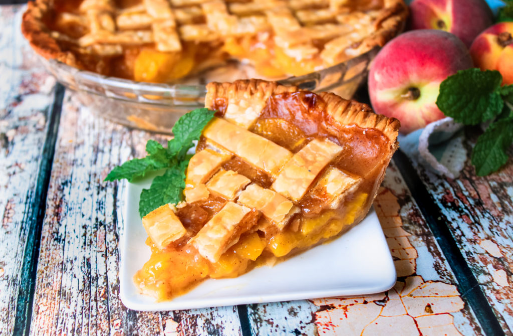 A slice of fresh peach pie on a white plate