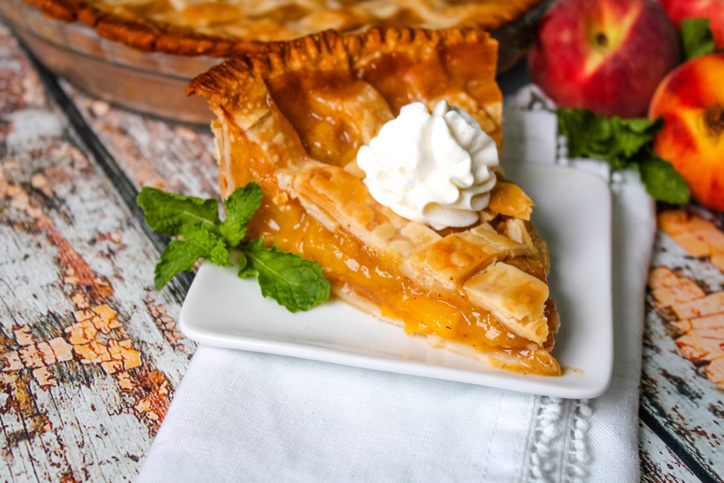 Slice of fresh peach pie on a while plate with whipped cream