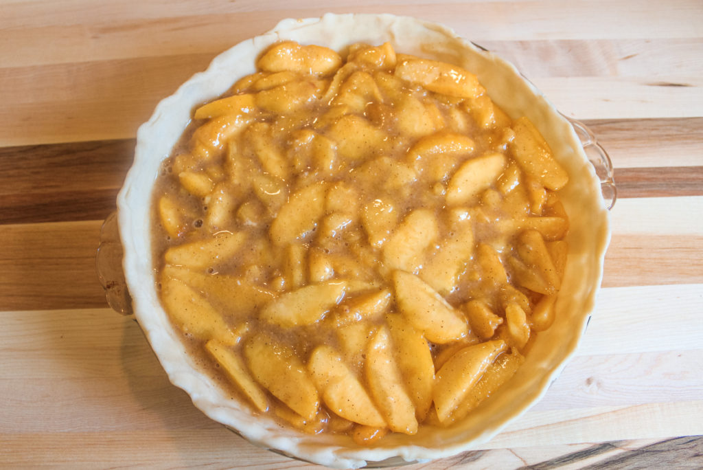 Fresh peach pie filling in the bottom crust
