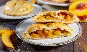 Peach hand pie cut in half on a plate