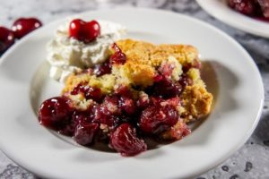 Wine Cherry Cobbler on a plate with whipped cream