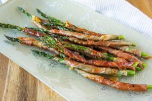 grilled prosciutto wrapped asparagus on a plate