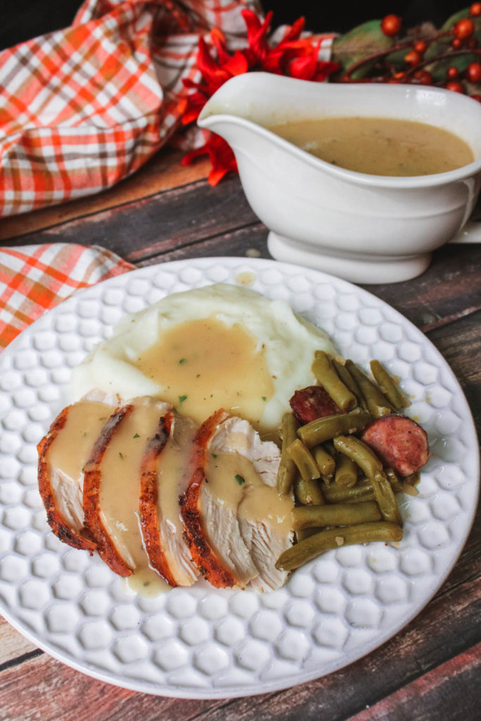 Gravy in gravy boat and gravy poured over a turkey dinner