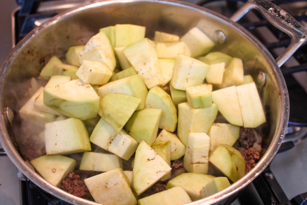 Peeled and diced eggplant added to the ground meat mixture.
