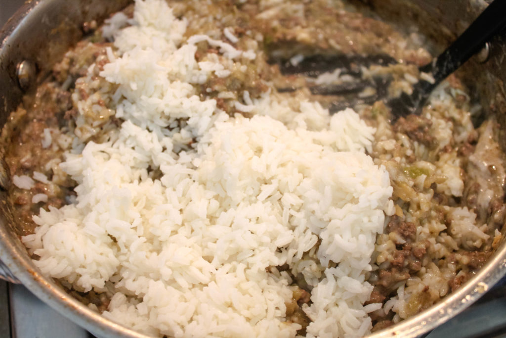 slowly adding rice to the eggplant mixture