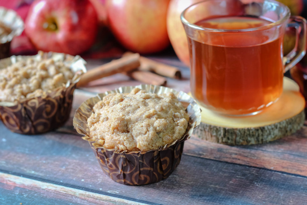 Apple Crumb Muffins next to a cup of tea.