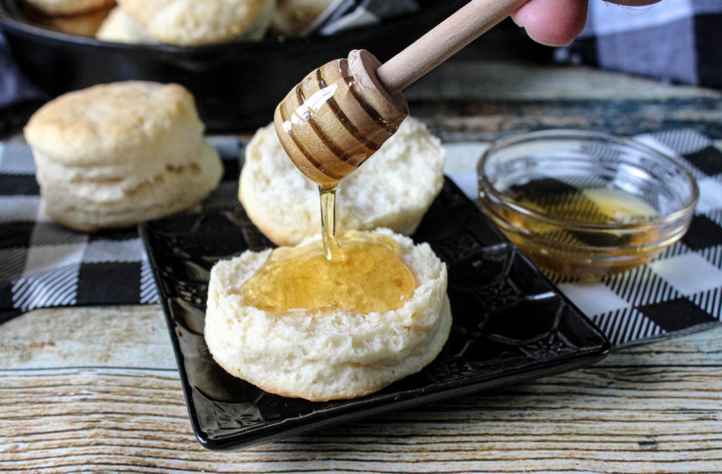 Honey being drizzled on biscuits
