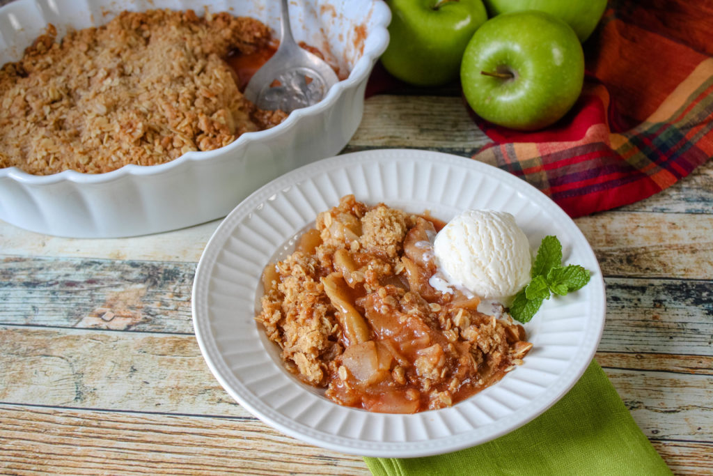 Cinnamon Apple Crisp in a white bowl topped with ice cream.