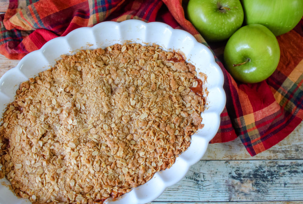 Baked Cinnamon Apple Crisp in a white casserole dish next to green apples
