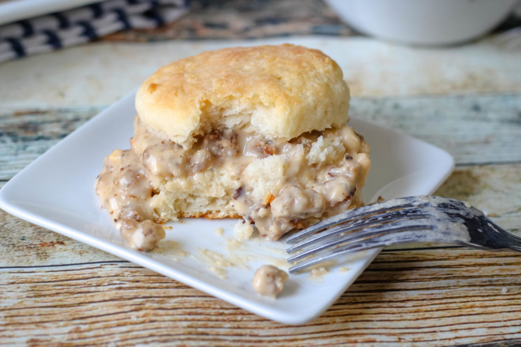 Sausage gravy and a biscuit with a bite taken out