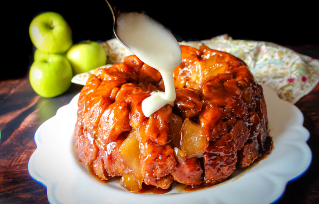 Drizzling the apple pie monkey bread with the icing