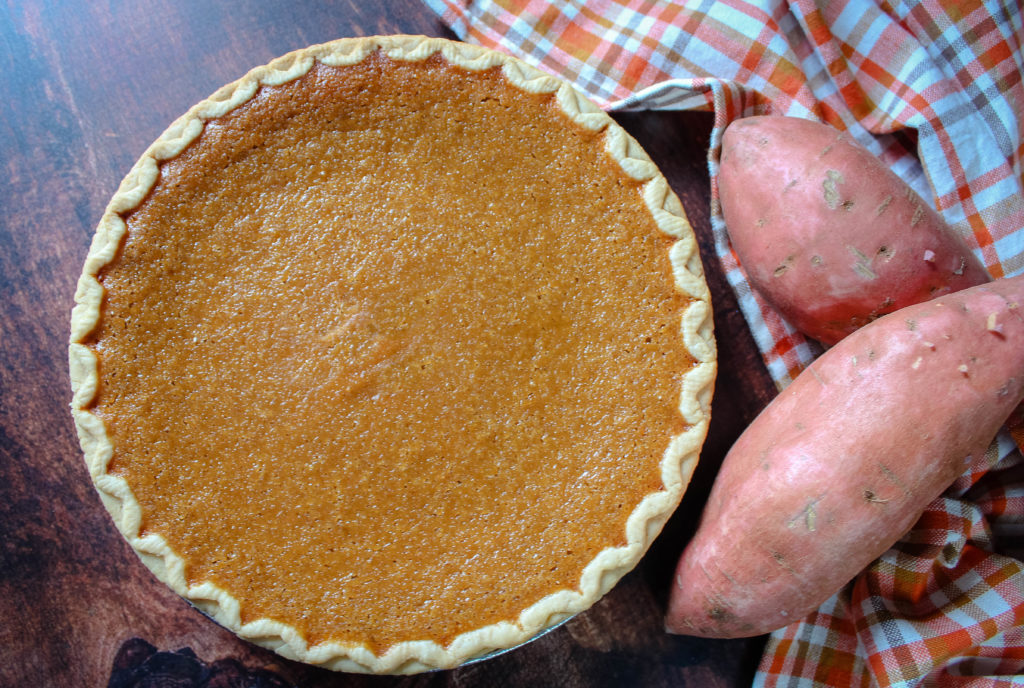 Southern Sweet Potato Pie on a table next to fresh potatoes