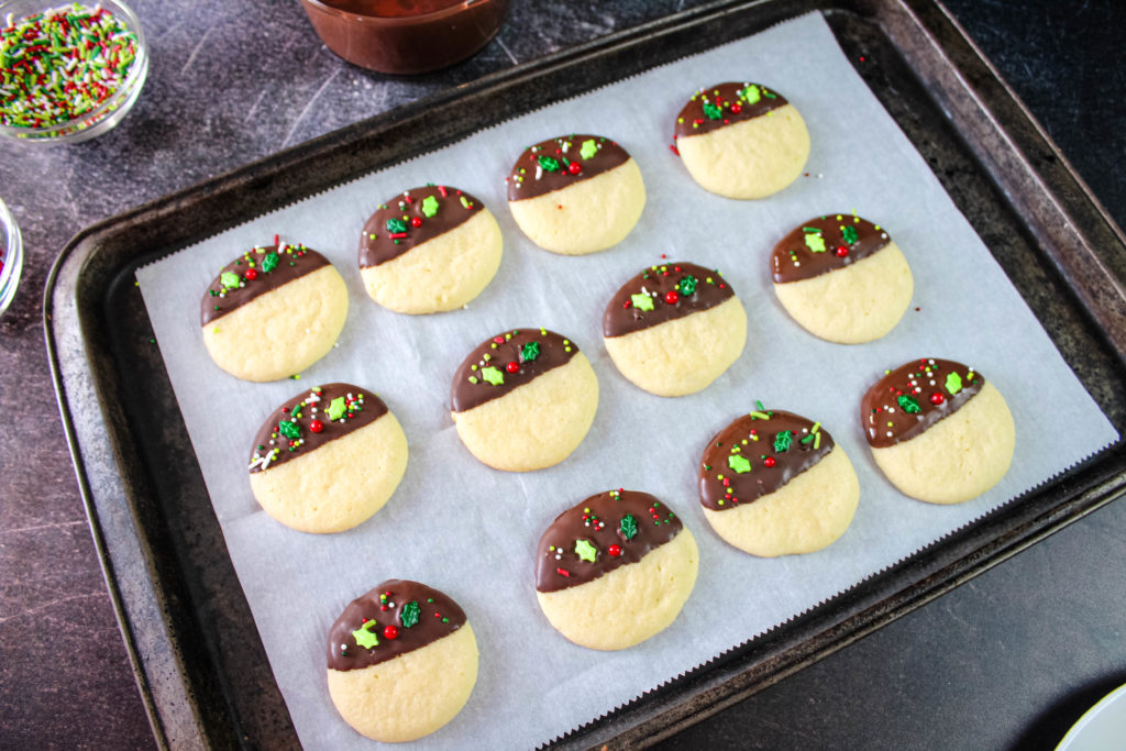 A tray full of Chocolate dipped sugar cookie with sprinkles drying on parchment paper