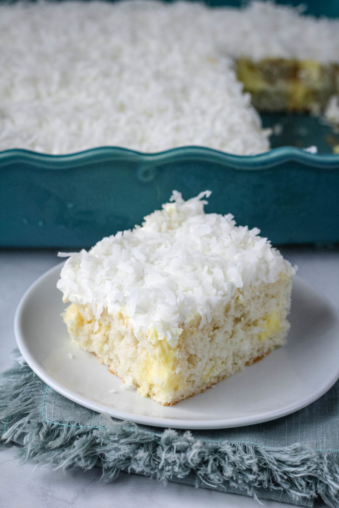 A slice of coconut poke cake on a white plate