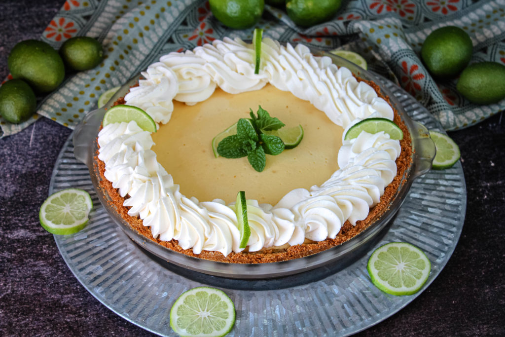 Creamy Key lime pie on a plate surrounded by limes