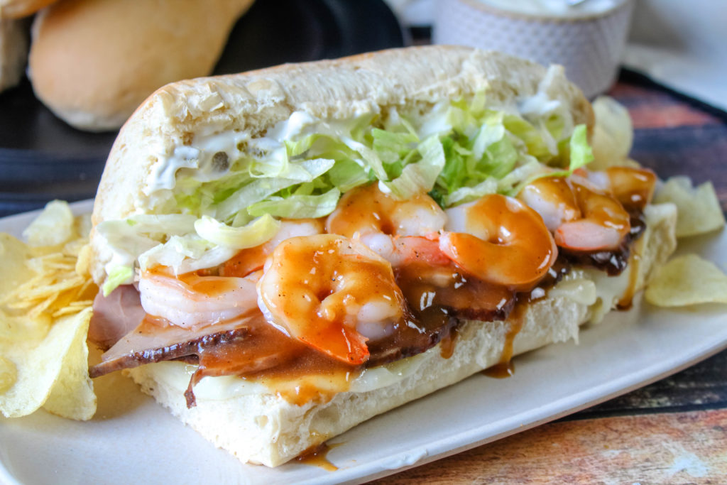 Surf and Turf Po'Boys on a plate with chips