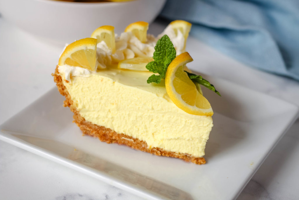 A slice of Lemon Pie on a white plate . The slice is garnished with Lemons and mint leaves