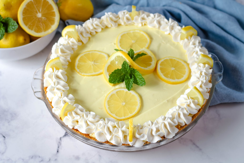 Lemon Cream Pie garnished with lemons and mint leaves next to a white bowl filled with lemons.