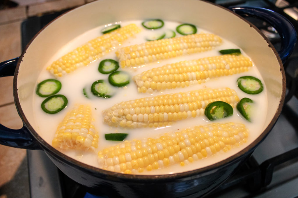 Sliced jalapenos in a pot with corn and milk