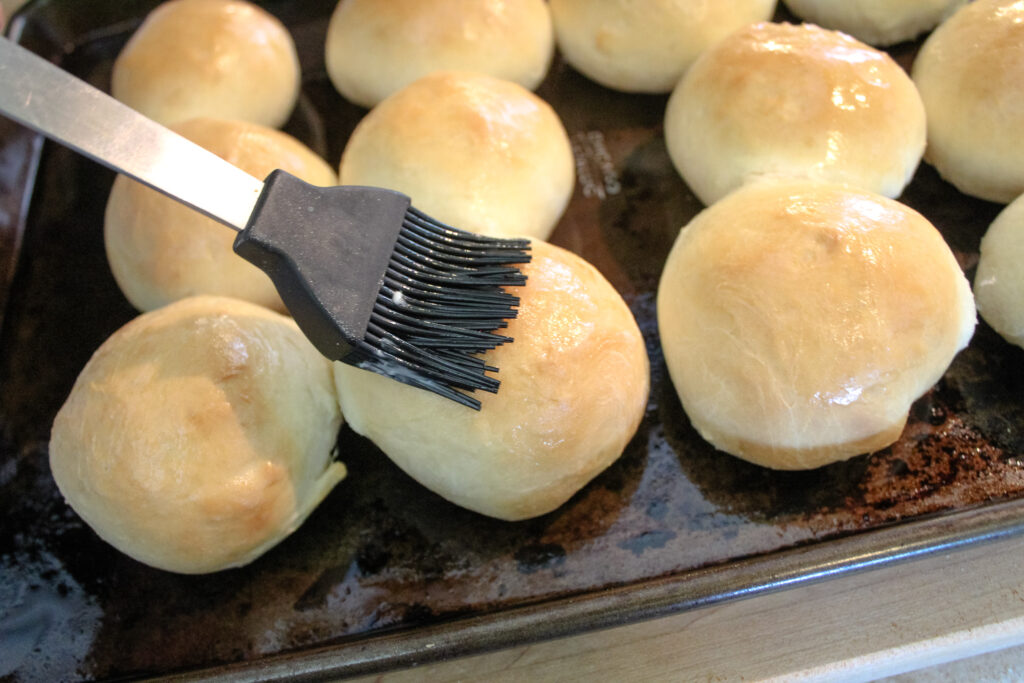Baked Hot Rolls being brushed with butter