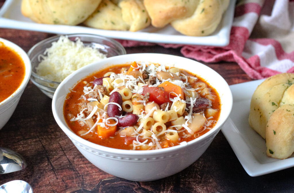 Easy Pasta e Fagioli in a white bowl with grated cheese on top.